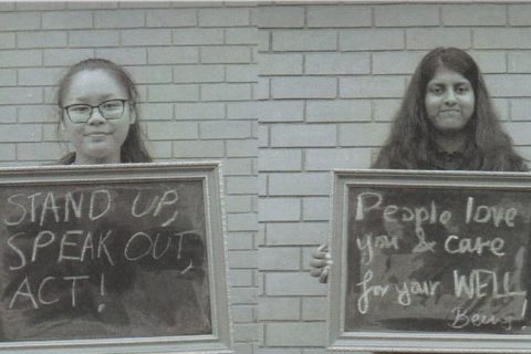 Two students holding chalkboards with the text Stand up, speak out, act!